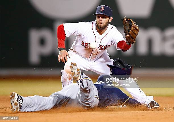 Dustin Pedroia of the Boston Red Sox misses the ball in front of a stealing Jean Segura of the Milwaukee Brewers at second base in the 8th inning...
