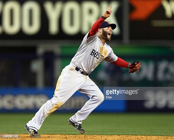 Dustin Pedroia of the Boston Red Sox points to the final out of the game against the New York Yankees as teammate Shane Victorino makes the catch on...