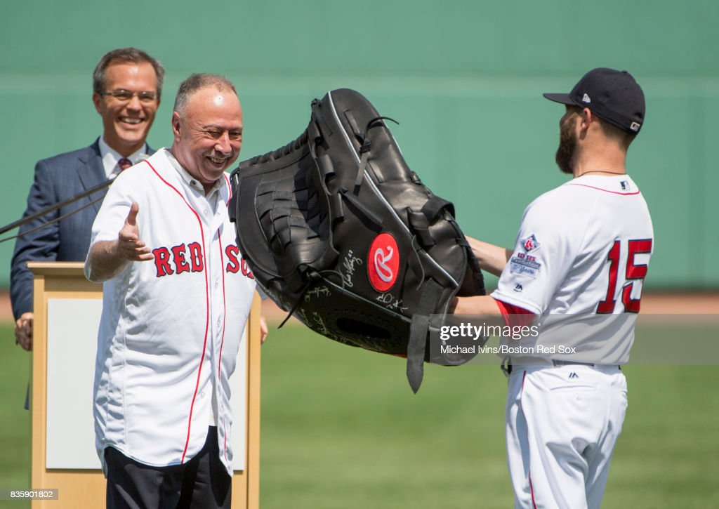 Dustin Pedroia #15 of the Boston Red Sox presents Jery Remy with an oversized baseball glove during a ceremony recognizing thirty years in the broadcast booth for the former second second baseman before a game against the New York Yankees at Fenway Park on August 20, 2017 in Boston, Massachusetts.