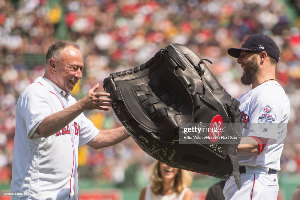 Dustin Pedroia #15 of the Boston Red Sox presents NESN broadcaster Jerry Remy with a giant glove as a gift during a 30 year recognition ceremony before a game between the Boston Red Sox and the New York Yankees on August 20, 2017 at Fenway Park in Boston, Massachusetts.
