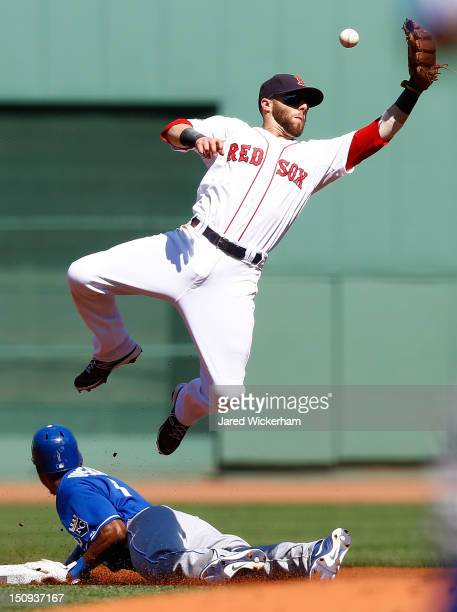 Dustin Pedroia of the Boston Red Sox reaches for a throw on a steal by Jarrod Dyson of the Kansas City Royal during the game on August 27 2012 at...