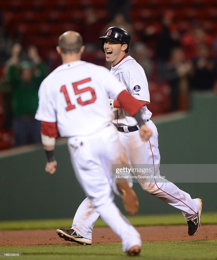 Dustin Pedroia #15 of the Boston Red Sox runs to congratulate Stephen Drew #7 after he hit a game-winning RBI double against the Minnesota Twins in the eleventh inning on May 6, 2013 at Fenway Park in Boston, Massachusetts.
