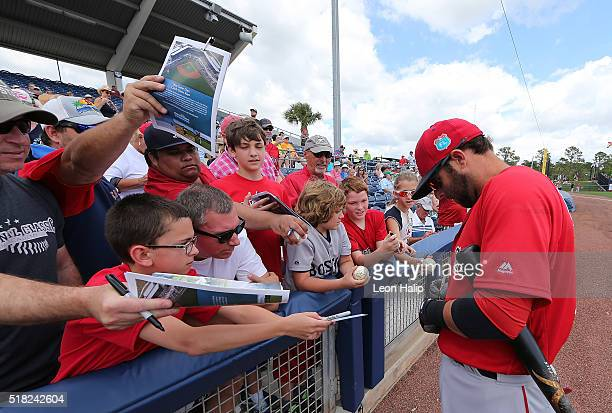 Dustin Pedroia of the Boston Red Sox signs autographs for fans prior to the star of the Spring Training Game against the Tampa Bay Rays on March 30...