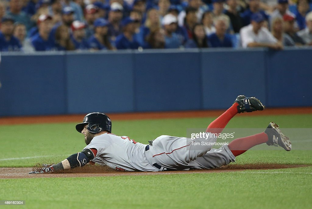 Dustin Pedroia #15 of the Boston Red Sox slides into third base with a triple in the first inning during MLB game action against the Toronto Blue Jays on September 19, 2015 at Rogers Centre in Toronto, Ontario, Canada.