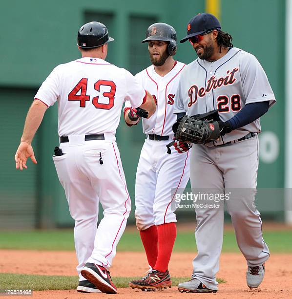 Dustin Pedroia of the Boston Red Sox stands at second base after a double as first base coach Arnie Beyeler helps with Pedroia's batting gloves and...