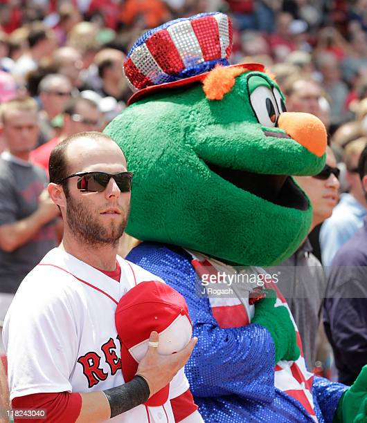 Dustin Pedroia of the Boston Red Sox stands next to team mascot Wally the Green Monster before a game against the Toronto Blue Jays at Fenway Park on...