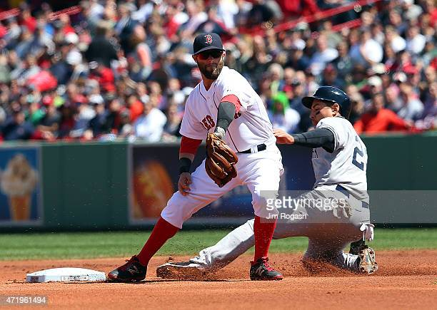 Dustin Pedroia of the Boston Red Sox takes a late throw as Jacoby Ellsbury of the New York Yankees steals second base in the first inning at Fenway...