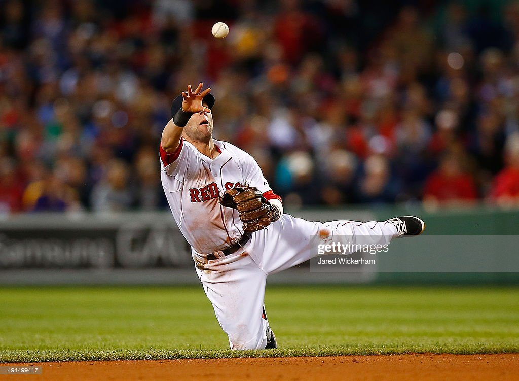 Dustin Pedroia #15 of the Boston Red Sox throws to second base from his knees against the Atlanta Braves during the game at Fenway Park on May 29, 2014 in Boston, Massachusetts.