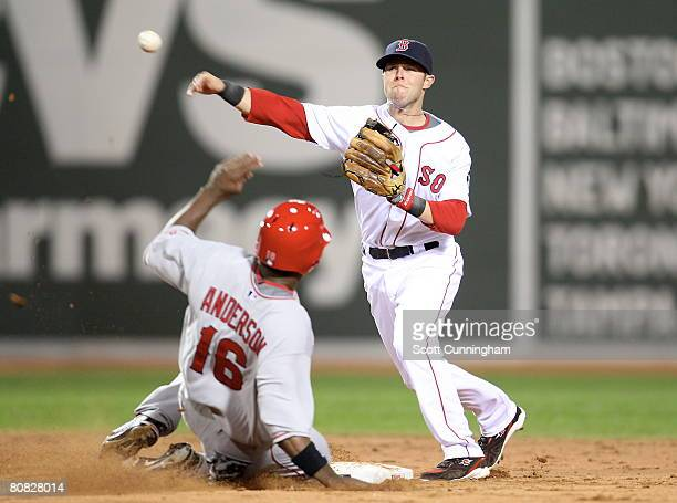 Dustin Pedroia of the Boston Red Sox turns a double play against Garret Anderson of the Los Angeles Angels at Fenway Park on April 22, 2008 in...
