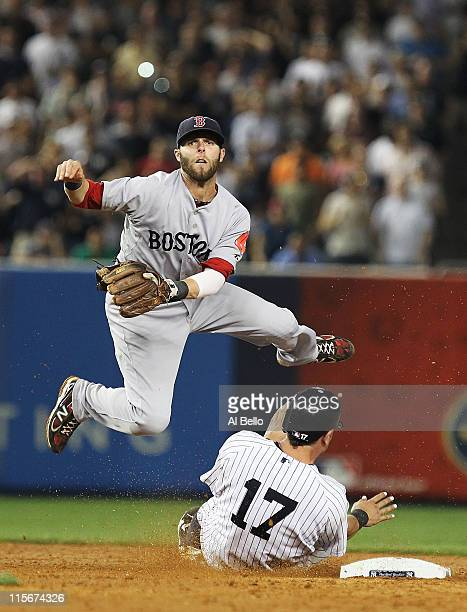Dustin Pedroia of the Boston Red Sox turns a double play as Francisco Cervelli of the New York Yankees slides into second base during their game on...