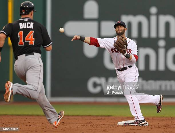 Dustin Pedroia of the Boston Red Sox turns a double play as John Buck of the Miami Marlins is out at second during interleague play at Fenway Park...