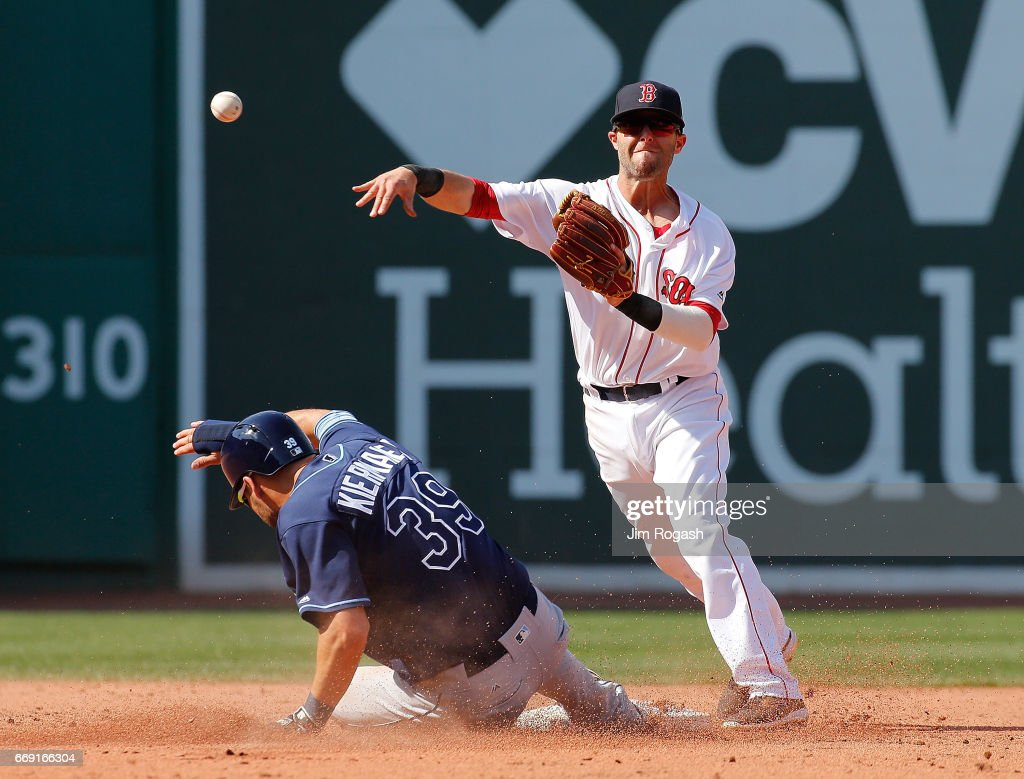 Dustin Pedroia #15 of the Boston Red Sox turns a double play as Kevin Kiermaier #39 of the Tampa Bay Rays slides late in the fifth inning at Fenway Park on April 16, 2017 in Boston, Massachusetts.