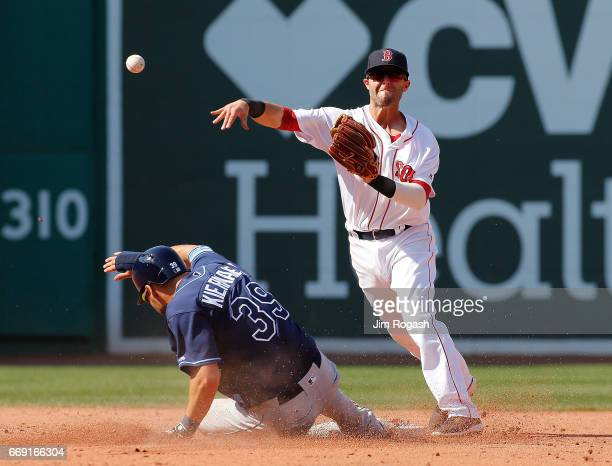 Dustin Pedroia of the Boston Red Sox turns a double play as Kevin Kiermaier of the Tampa Bay Rays slides late in the fifth inning at Fenway Park on...