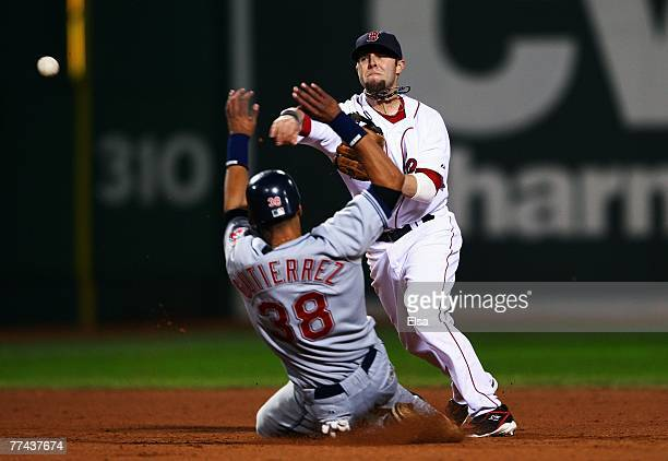 Dustin Pedroia of the Boston Red Sox turns an inning ending double play against Franklin Gutierrez and the Cleveland Indians in the seventh inning of...