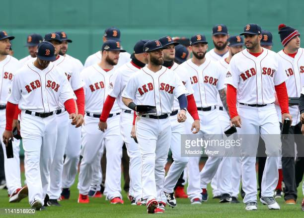 Dustin Pedroia of the Boston Red Sox walks on the field with his World Series ring before the home opener against the Toronto Blue Jays at Fenway...
