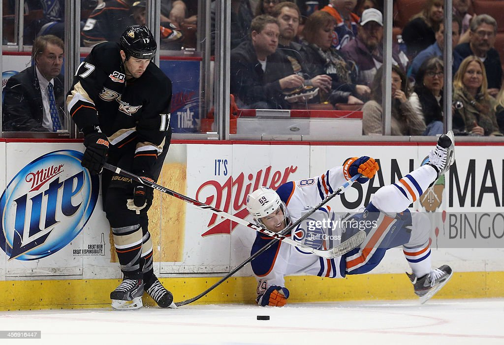 Dustin Penner #17 of the Anaheim Ducks checks Sam Gagner #89 of the Edmonton Oilers off the puck in the third period at Honda Center on December 15, 2013 in Anaheim, California. The Ducks defeated the Oilers 3-2.