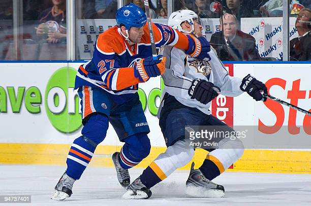 Dustin Penner of the Edmonton Oilers holds up Kevin Klein of the Nashville Predators in the neutral zone at Rexall Place on December 17 2009 in...
