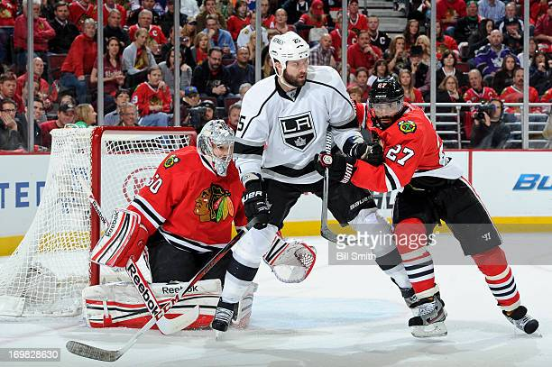 Dustin Penner of the Los Angeles Kings and Johnny Oduya of the Chicago Blackhawks fight for position in front of the goal in Game Two of the Western...