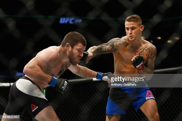 Dustin Poirier of United States lands a punch against Jim Miller of United States in the first round of their lightweight bout during UFC 208 at the...