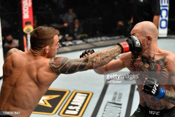 Dustin Poirier punches Conor McGregor of Ireland in a lightweight fight during the UFC 257 event inside Etihad Arena on UFC Fight Island on January...