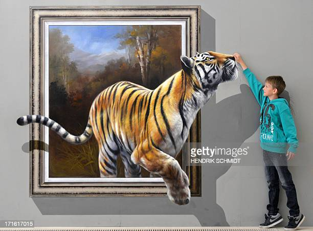 Dustin poses next to an art work depicting a tiger and created in a special 3Dtechnique by a ChineseKorean artist group on June 27 2013 at the...