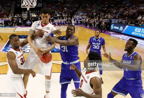 Dustin Thomas of the Arkansas Razorbacks and Angel Delgado of the Seton Hall Pirates battle for a rebound in the first round of the 2017 NCAA Men's...