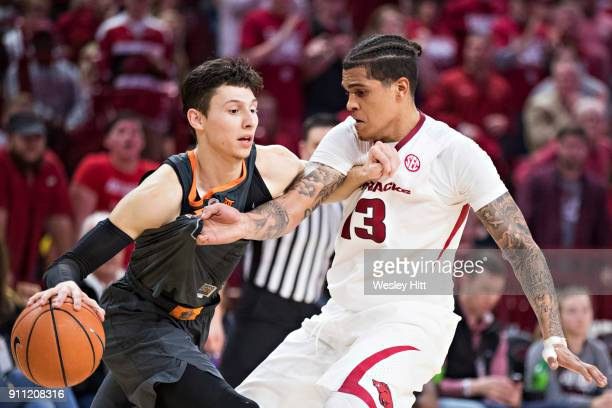 Dustin Thomas of the Arkansas Razorbacks is called for a foul while trying to make a steal from Lindy Waters III of the Oklahoma State Cowboys at Bud...