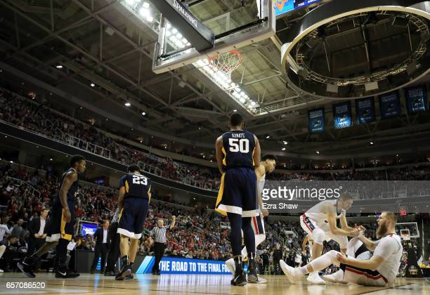 Dustin Triano helps Przemek Karnowski of the Gonzaga Bulldogs to his feet in the second half against the West Virginia Mountaineers during the 2017...