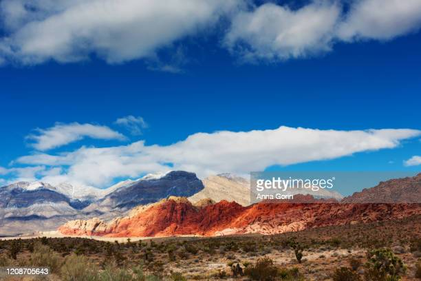 dusting of snow on mountains at red rock canyon outside las vegas, nevada, in winter - nevada stock-fotos und bilder