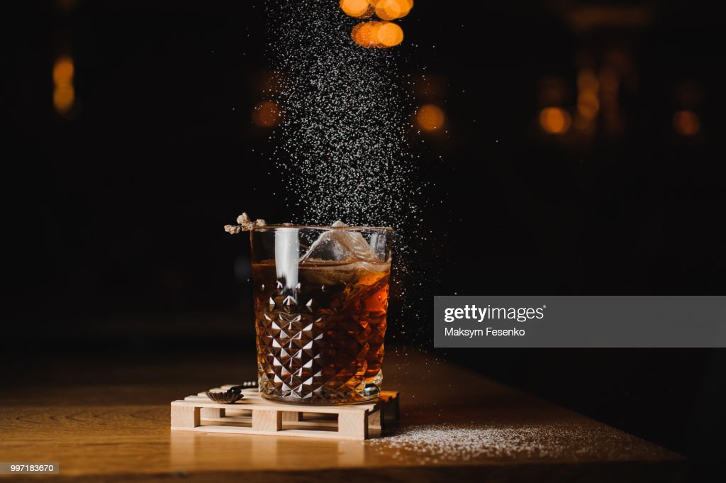 dusting whiskey drink with  ice  on  wood in bar : Foto de stock