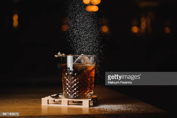 dusting whiskey drink with  ice  on  wood in bar - whisky stock photos and pictures