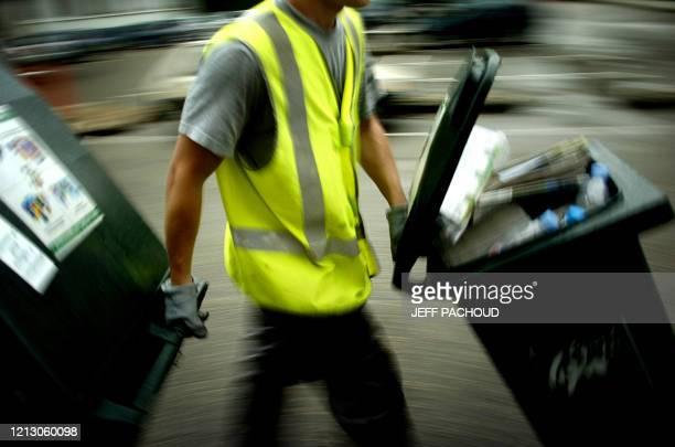 Dustman brings dumpsters to a waste truck, 06 July in Lyon, south France. Un éboueur amène des bennes, le 06 juillet 2006 à Lyon, vers le camion de...