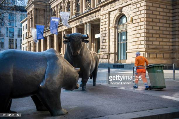 Dustman carries a dustbin next to the bull statue and a bear statue outside the Frankfurt Stock Exchange on March 19, 2020 in Frankfurt, Germany....