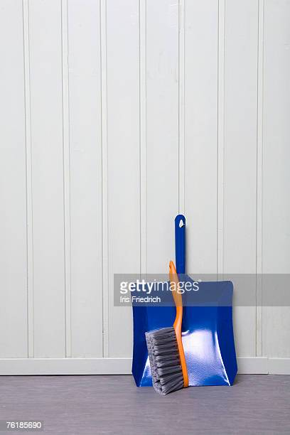 A dustpan and broom in a corner