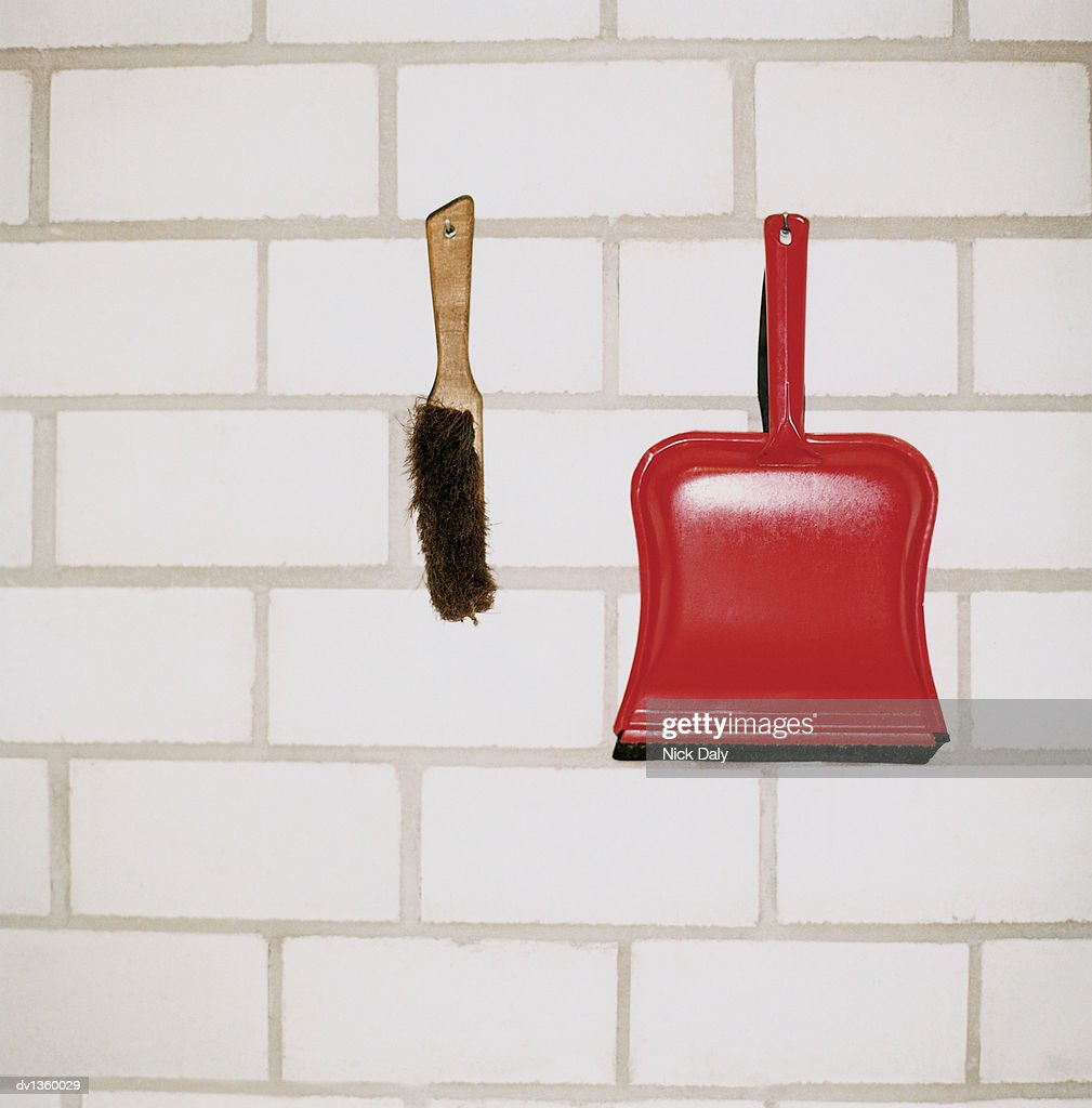 Dustpan And Brush Hanging From Hooks On A Brick Wall Stock Photo