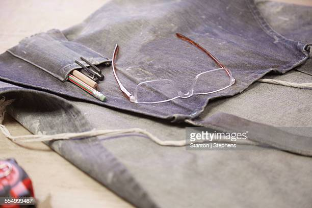 Dusty apron and eye glasses in cabinet makers workshop