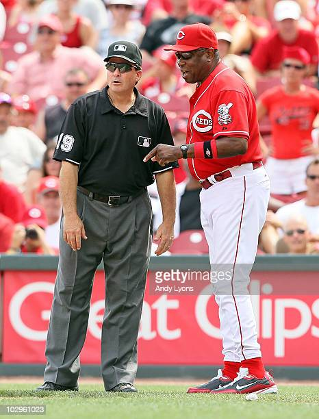Dusty Baker the manager of the Cincinnati Reds talks with first base umpire Ed Rapuano about a play during the game against the Colorado Rockies at...