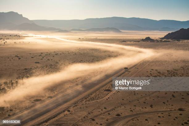 Dusty dirt road at sunrise. Aerial view, Namibia.