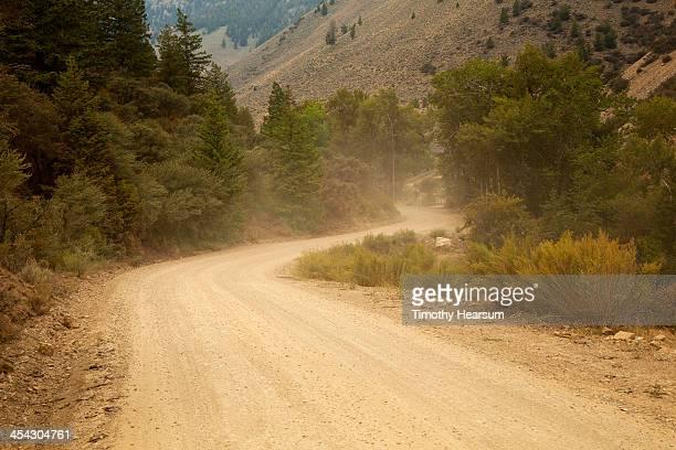 dusty dirt road climbing a hillside - timothy hearsum stock-fotos und bilder