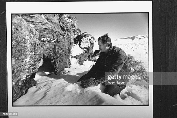 Dusty Ferguson kneeling on the snowy ground by cave where he rescued Jennifer Stolpa her 5moold son Clayton who were using the cave for shelter after...