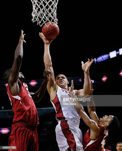 Dusty Hannahs and Jabril Durham of the Arkansas Razorbacks defend the basket against Reid Travis of the Stanford Cardinal at Barclays Center on...