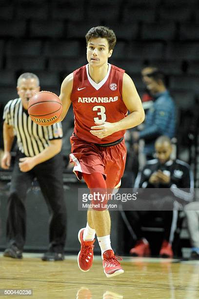 Dusty Hannahs of the Arkansas Razorbacks dribbles up court during the consolation game of the NIT Season TipOff college basketball tournament against...