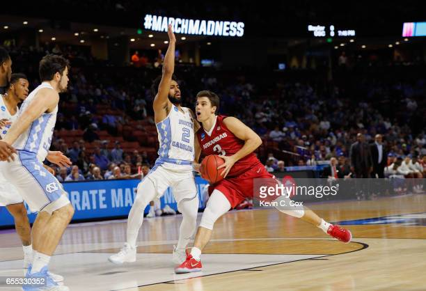 Dusty Hannahs of the Arkansas Razorbacks drives against Joel Berry II of the North Carolina Tar Heels in the first half during the second round of...