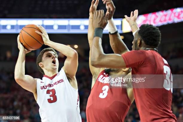 Dusty Hannahs of the Arkansas Razorbacks goes up for shot against Corban Collins and Donta Hall of the Alabama Crimson Tide at Bud Walton Arena on...