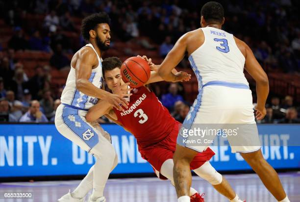 Dusty Hannahs of the Arkansas Razorbacks is fouled as he drives against Joel Berry II and Kennedy Meeks of the North Carolina Tar Heels in the first...