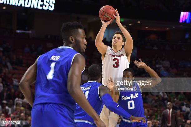 Dusty Hannahs of the Arkansas Razorbacks puts up a shot against Angel Delgado and Khadeen Carrington of the Seton Hall Pirates during the first round...