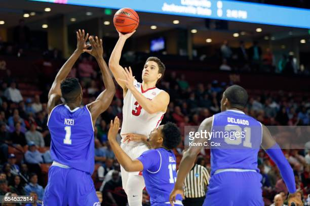 Dusty Hannahs of the Arkansas Razorbacks shoots over Michael Nzei and Myles Powell of the Seton Hall Pirates in the first half in the first round of...