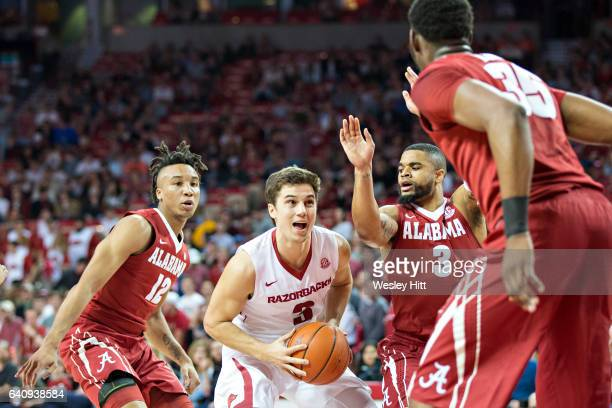 Dusty Hannahs of the Arkansas Razorbacks tries to go up for shot against Corban Collins and Dazon Ingram of the Alabama Crimson Tide at Bud Walton...