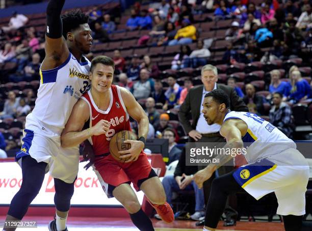 Dusty Hannahs of the Memphis Hustle handles the ball between Marcus Derrickson and Michael Gbinije of the Santa Cruz Warriors at Landers Center in an...