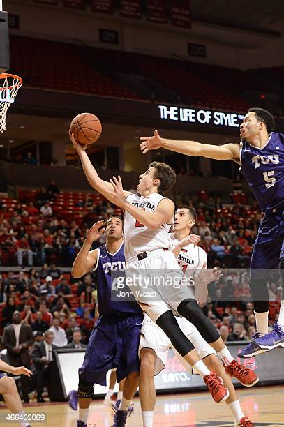 Dusty Hannahs of the Texas Tech Red Raiders goes to the basket in between Amric Fields of the TCU Horned Frogs and Kyan Anderson of the TCU Horned...